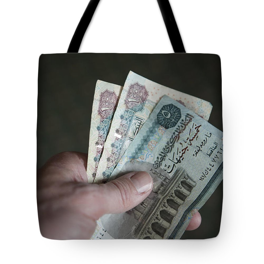 Egypt Tote Bag featuring the photograph A Hand Holds Egyptian Pounds In Cash by Taylor S. Kennedy