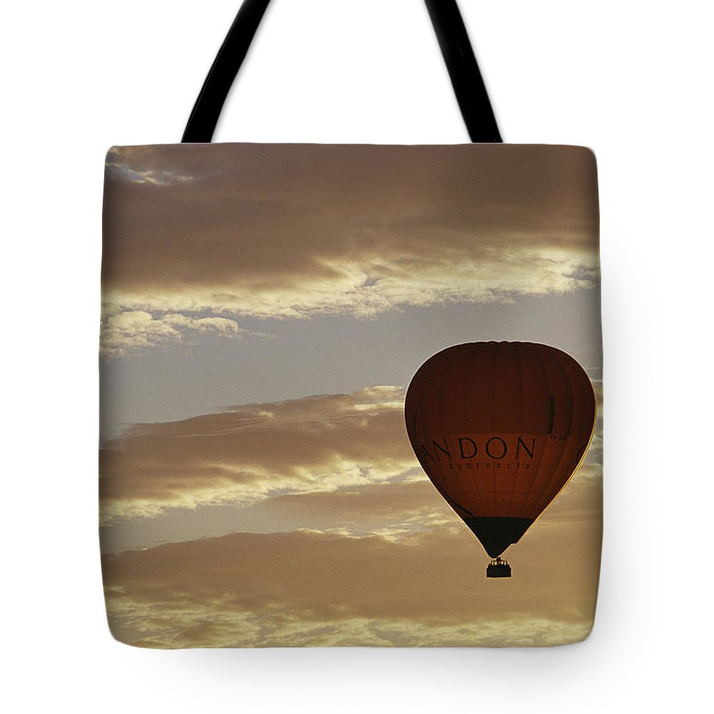 Clouds Tote Bag featuring the photograph A Soaring Hot Air Balloon by Jason Edwards