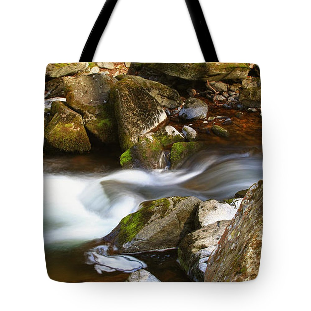 Flowing River Blurred Through Rocks Tote Bag featuring the photograph Flowing River Blurred Through Rocks by Simon Bratt Photography LRPS