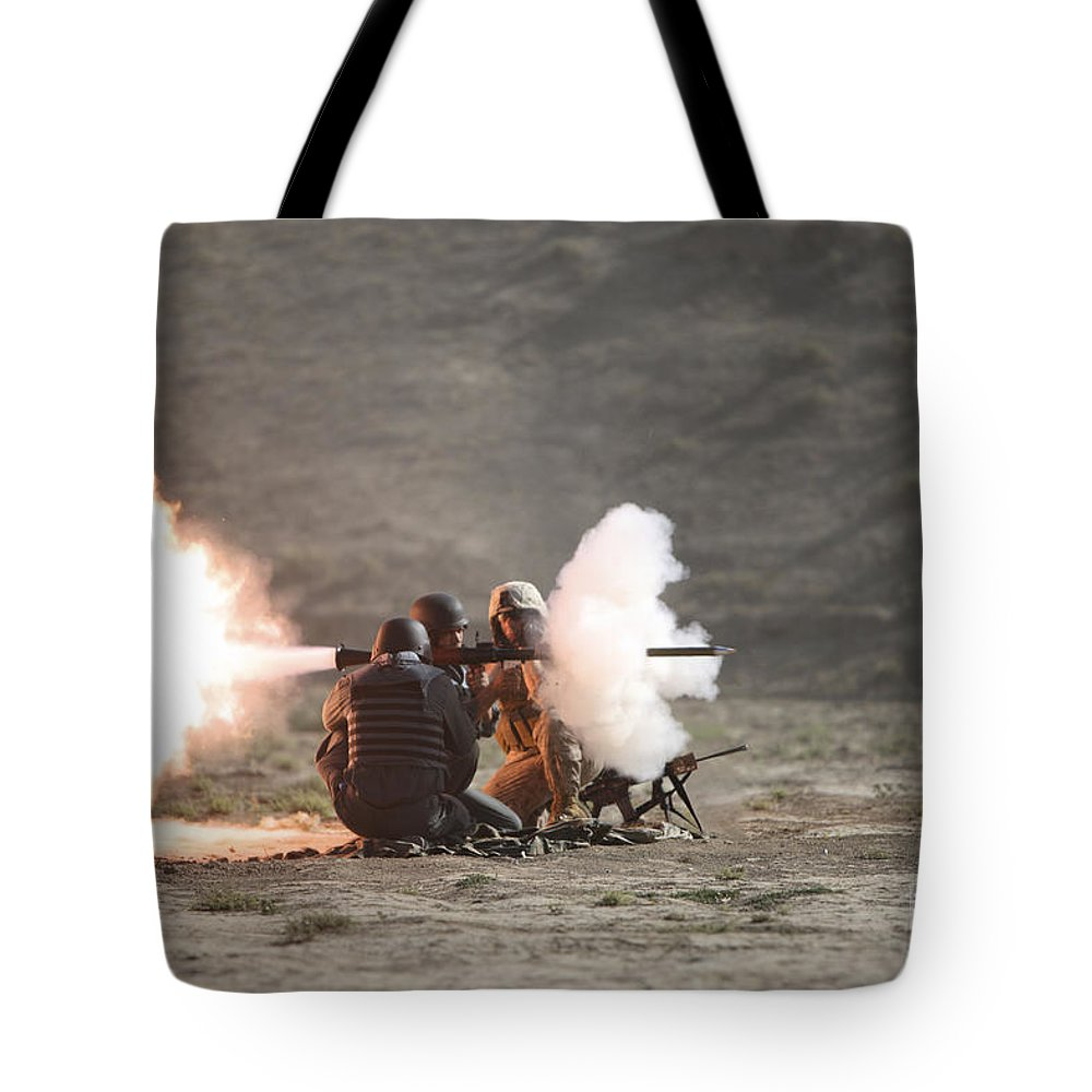 Afghan National Police Tote Bag featuring the photograph An Afghan Police Studen Fires by Terry Moore