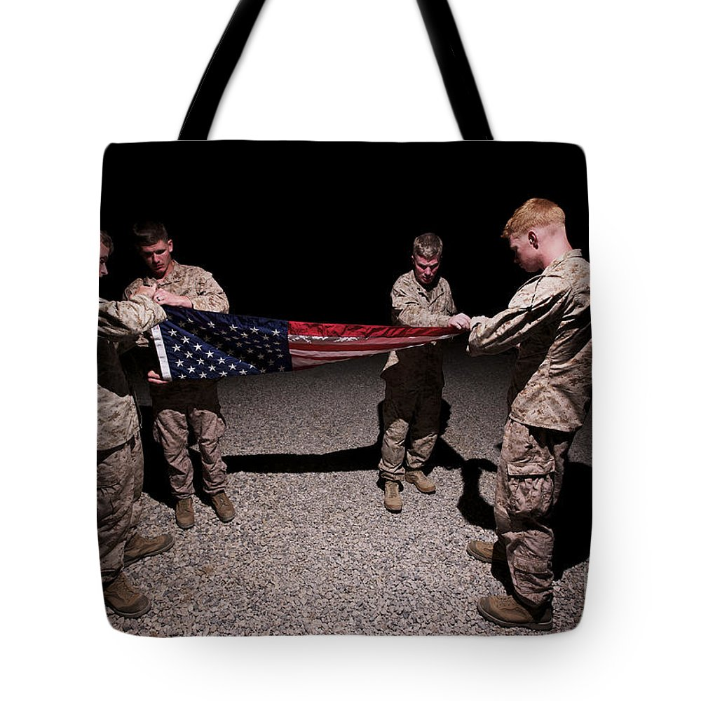 Flag Tote Bag featuring the photograph U.s. Marines Fold The American Flag by Terry Moore