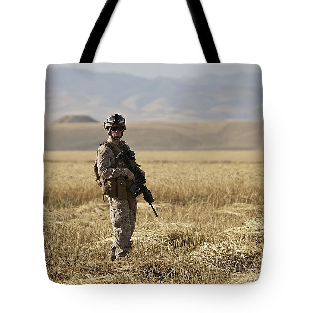 Patrol Tote Bag featuring the photograph U.s. Marine Patrols A Wadi Near Kunduz by Terry Moore