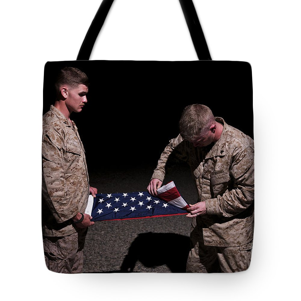 Afghanistan Tote Bag featuring the photograph U.s. Marines Fold The American Flag by Terry Moore