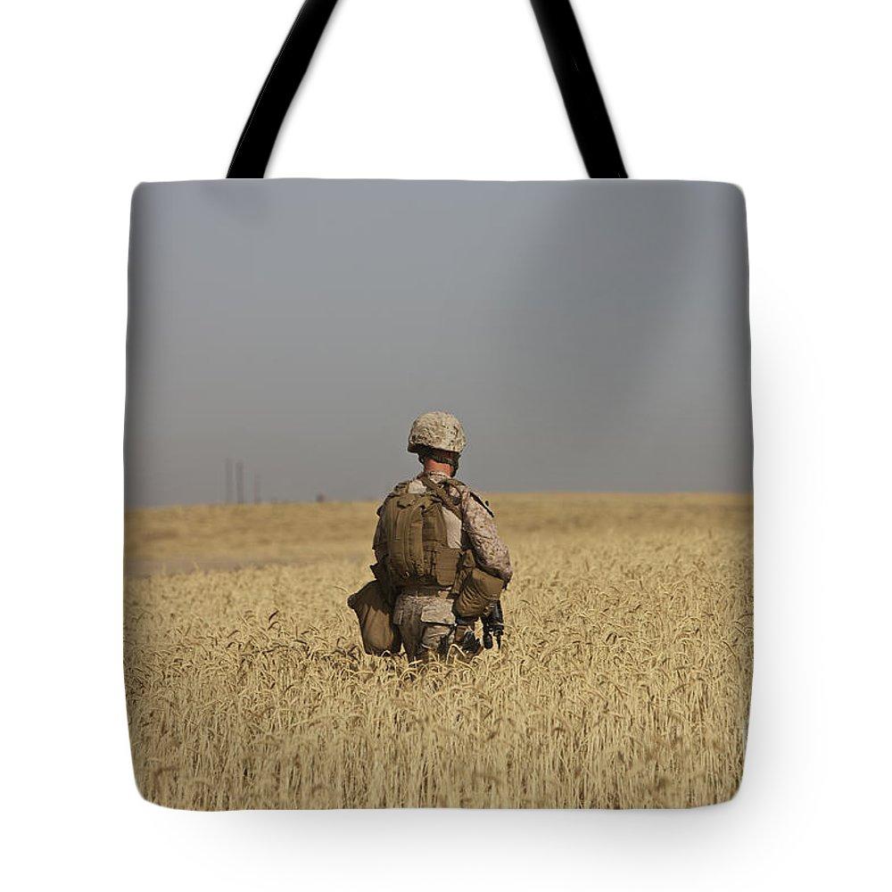 Wheat Tote Bag featuring the photograph U.s. Marine Patrols A Wadi Near Kunduz by Terry Moore