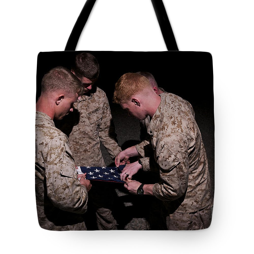 Us Flag Tote Bag featuring the photograph U.s. Marines Fold The American Flag by Terry Moore