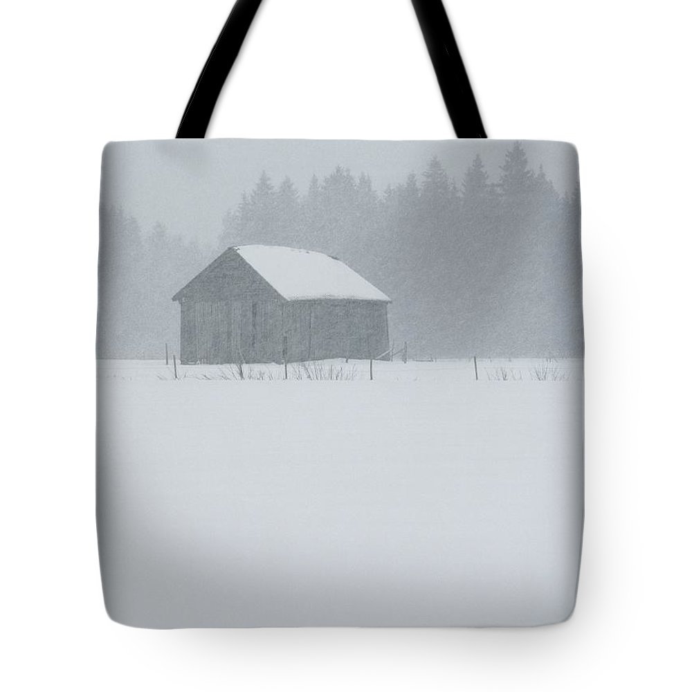 Natural Forces And Phenomena Tote Bag featuring the photograph A Barn Behind A Fence In The Snow by Mattias Klum