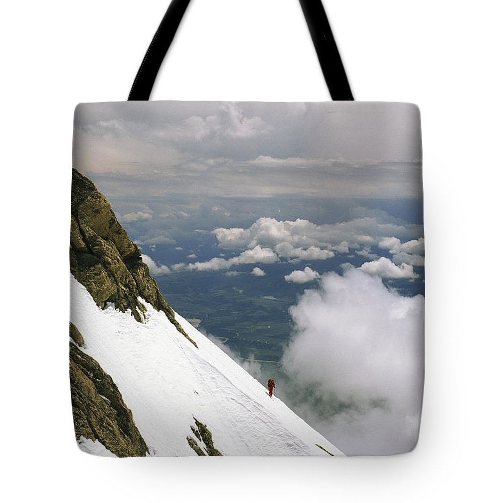 Color Image Tote Bag featuring the photograph A Climber Walks Along A Steep Slope by Gordon Wiltsie