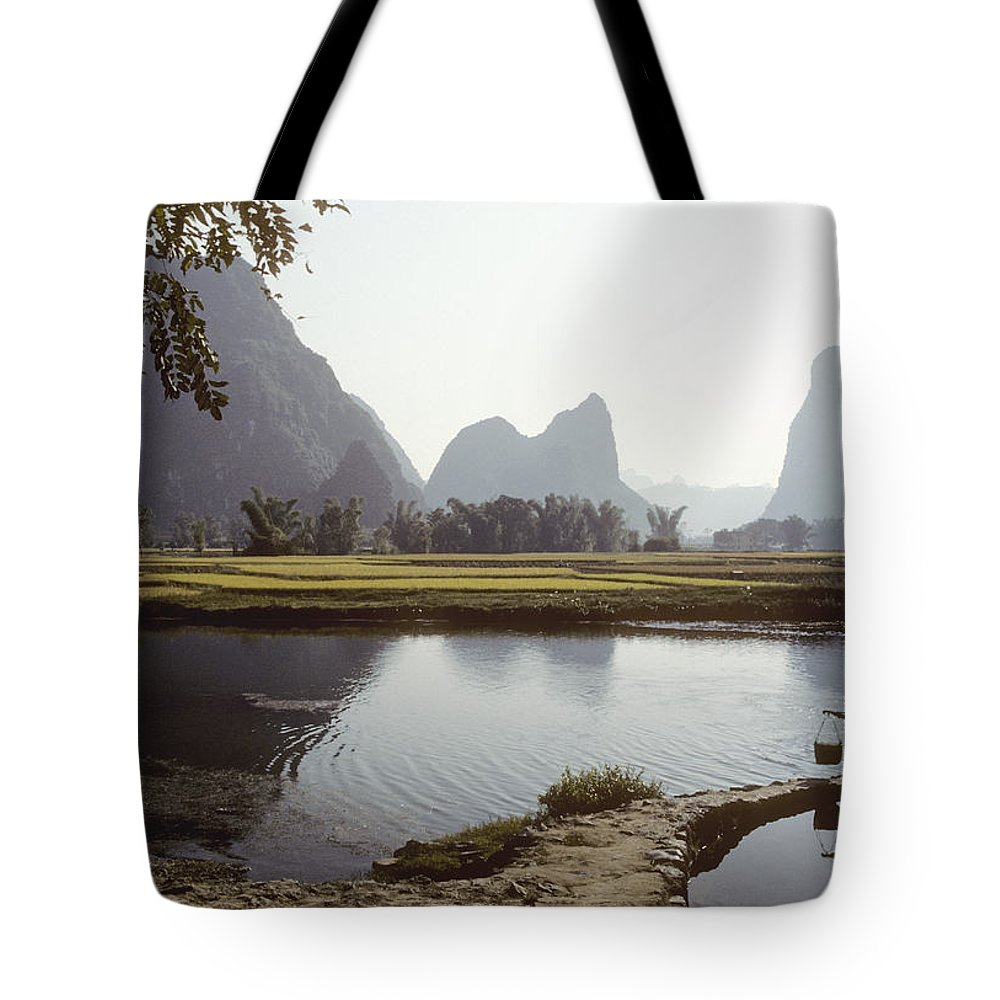 China Tote Bag featuring the photograph A Farm Worker Carries Water On Shoulder by Kenneth Ginn