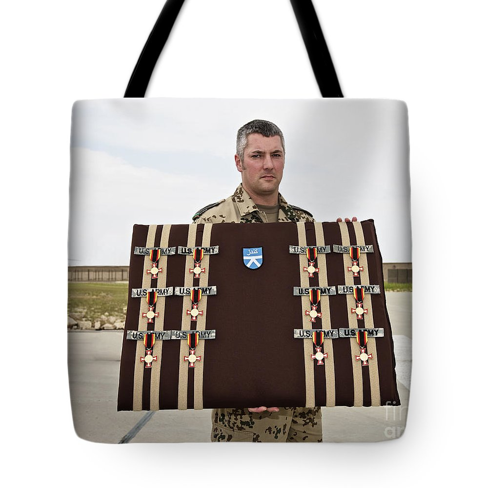 Afghanistan Tote Bag featuring the photograph A German Soldier Holds A Display by Terry Moore