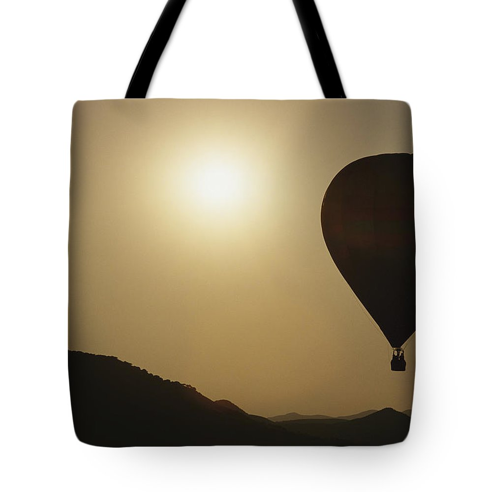 Scenes And Views Tote Bag featuring the photograph A Hot Air Balloon Rises Above A Hilly by Raul Touzon