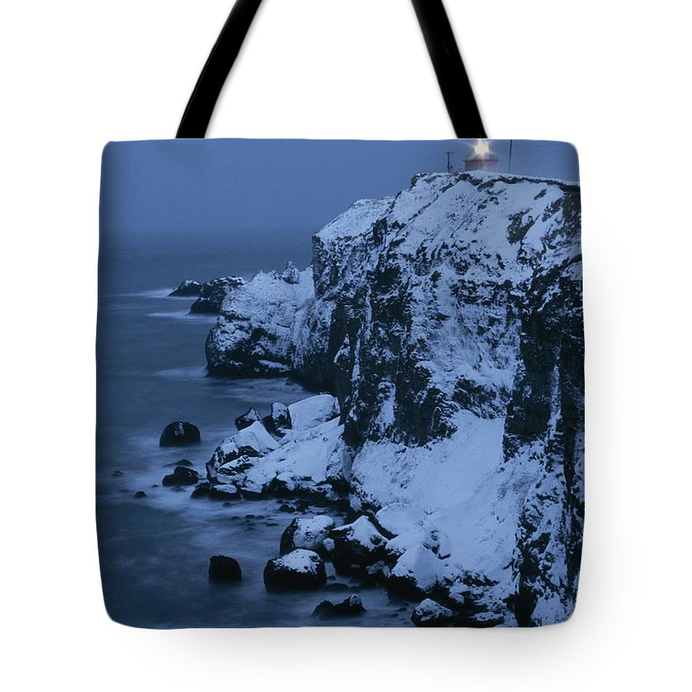 Structures Tote Bag featuring the photograph A Lighthouse Atop Snow-covered Cliffs by Tim Laman