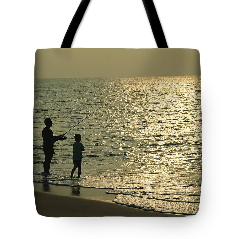 Fishing And Fishermen Tote Bag featuring the photograph A Man And A Young Boy Fish In The Surf by Medford Taylor