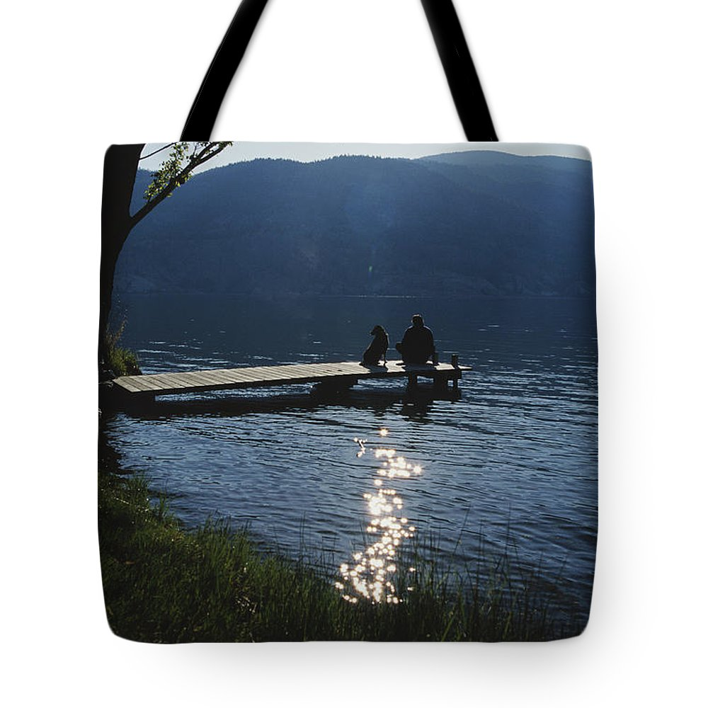 North America Tote Bag featuring the photograph A Man And His Dog On A Lake Skaha Dock by Mark Cosslett