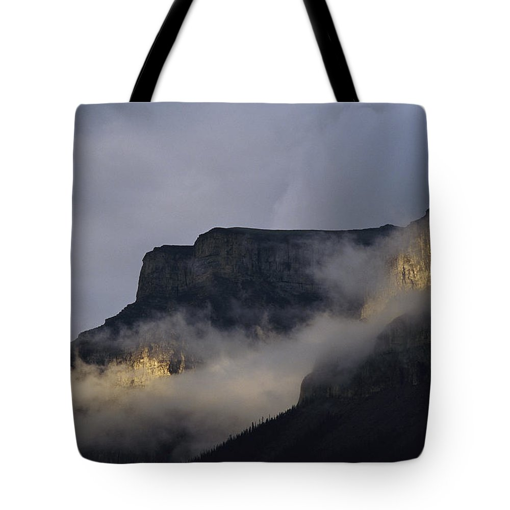 North America Tote Bag featuring the photograph A Mountain Peaks Through The Clouds by Stephen Alvarez