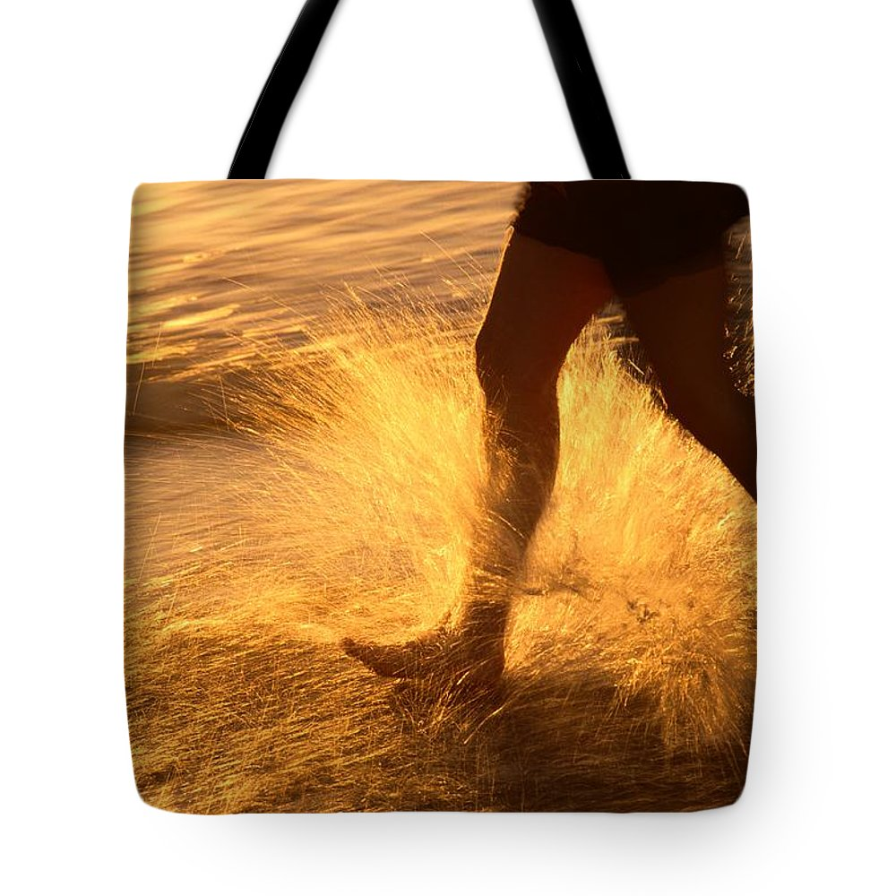 Outdoors Tote Bag featuring the photograph A Runner Splashing Through The Surf by Phil Schermeister