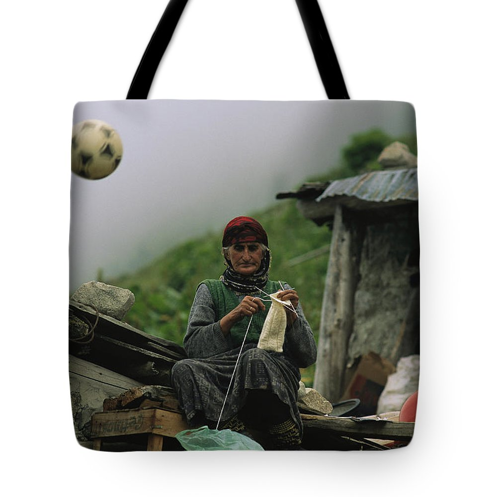 Peoples Tote Bag featuring the photograph A Soccer Ball Flies Over The Head by Randy Olson