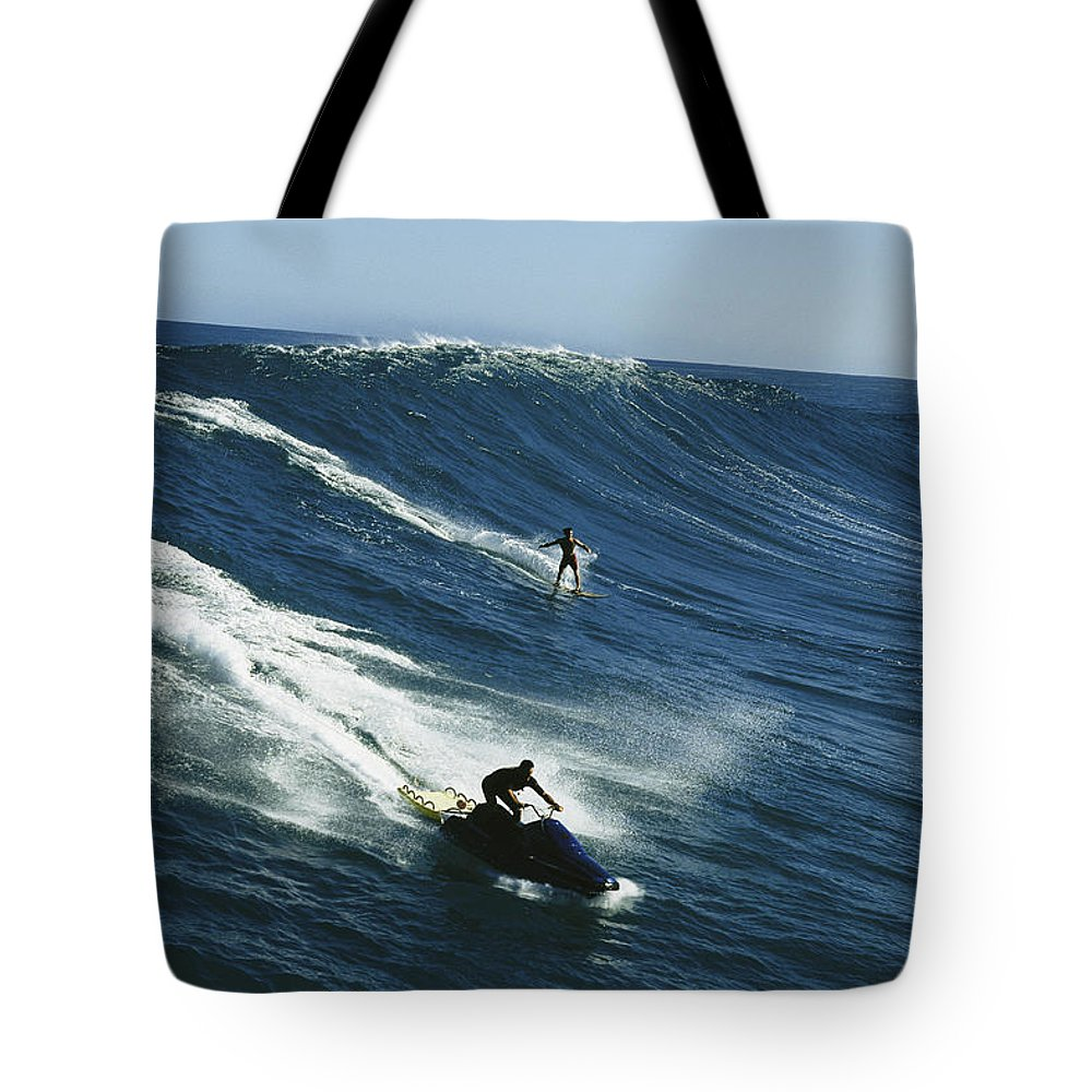 A Surfer And Jet-skier Off The North Shore Of Maui Island. Tote Bag featuring the photograph A Surfer And Jet-skier Off The North by Patrick Mcfeeley