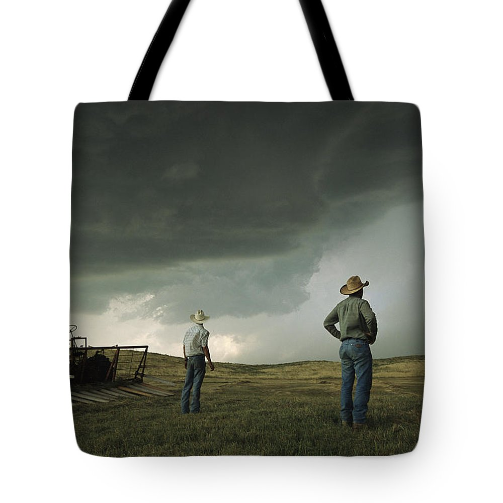 North America Tote Bag featuring the photograph A Thunderstorm Halts Haying As Two by Jim Richardson