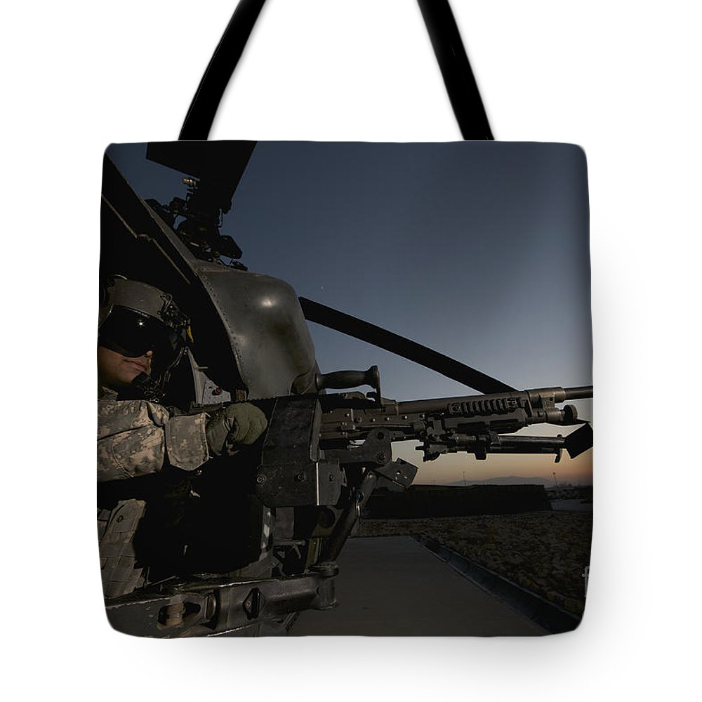 Helicopter Tote Bag featuring the photograph A Uh-60l Blackhawk Door Gunner Mans by Terry Moore