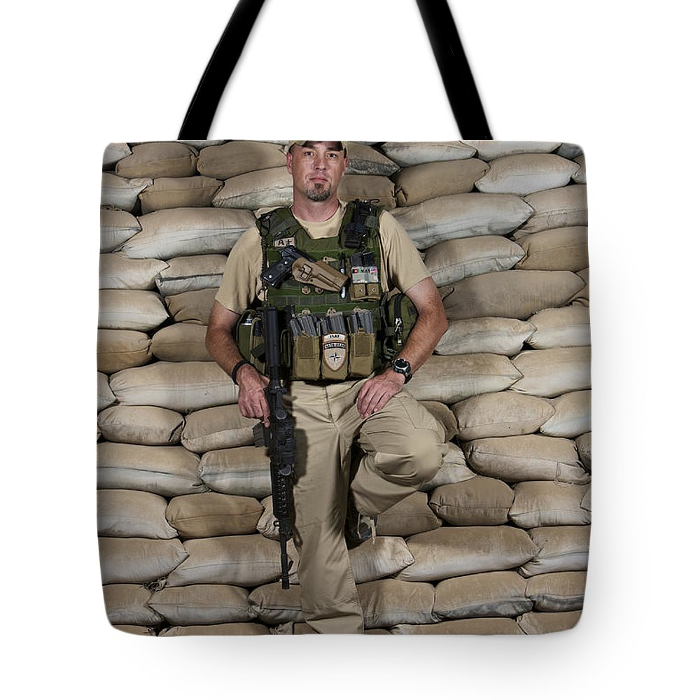 Operation Enduring Freedom Tote Bag featuring the photograph A U.s. Police Officer Contractor Leans by Terry Moore