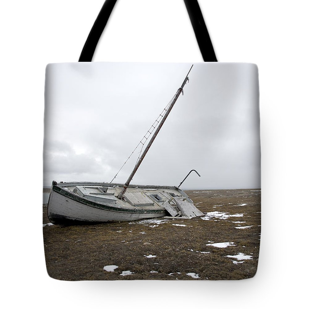 Arctic Tote Bag featuring the photograph A Wooden Sailboat Is Beached by Pete Ryan