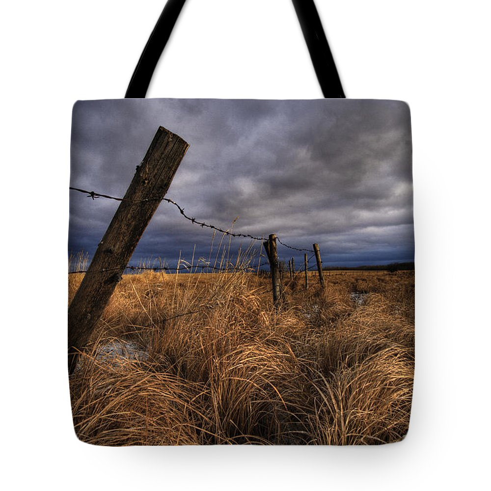 Barbed Wire Tote Bag featuring the photograph Barbed Wire Fence Posts With Dark Sky by Dan Jurak