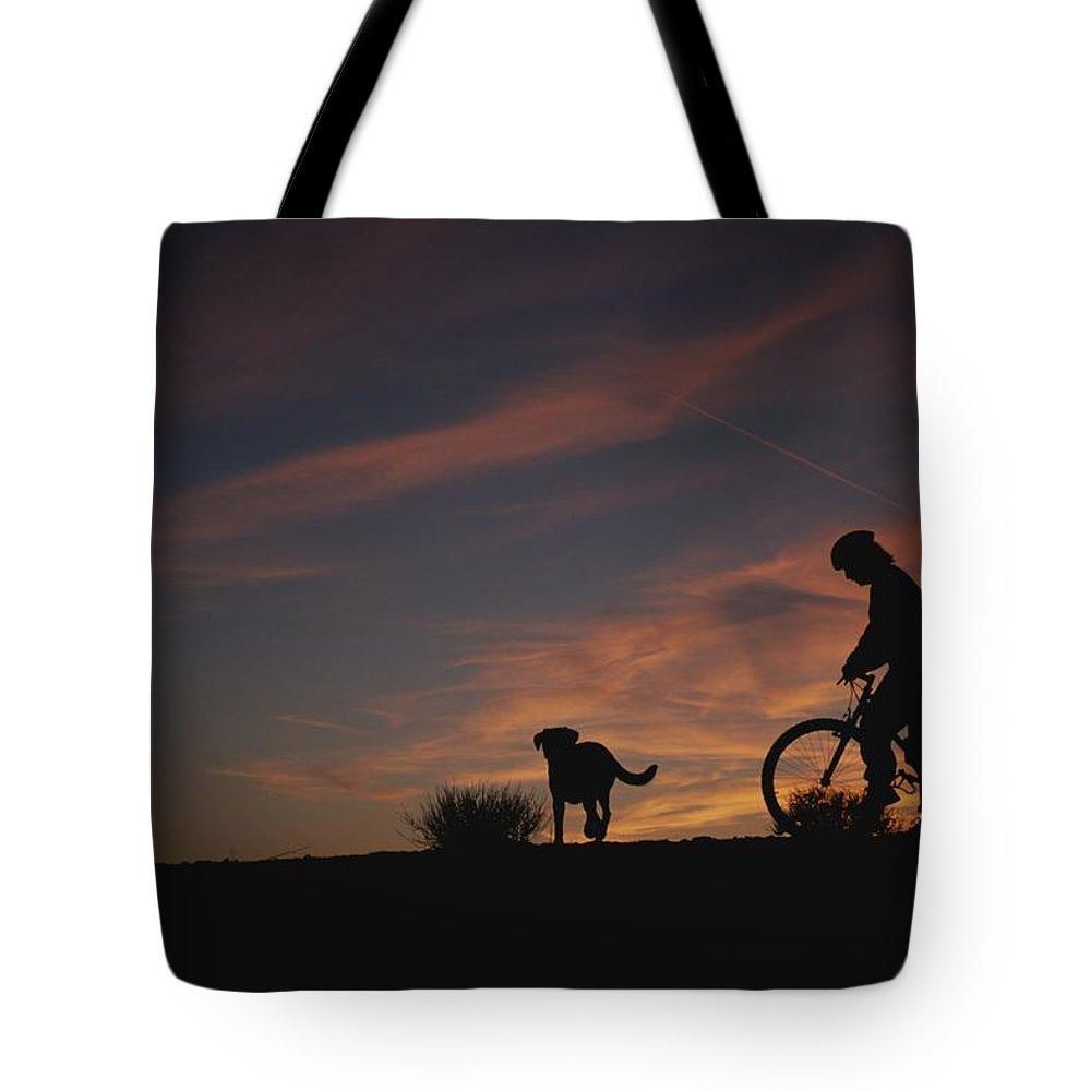 North America Tote Bag featuring the photograph Bicyclist And Pet Silhouetted by Bobby Model