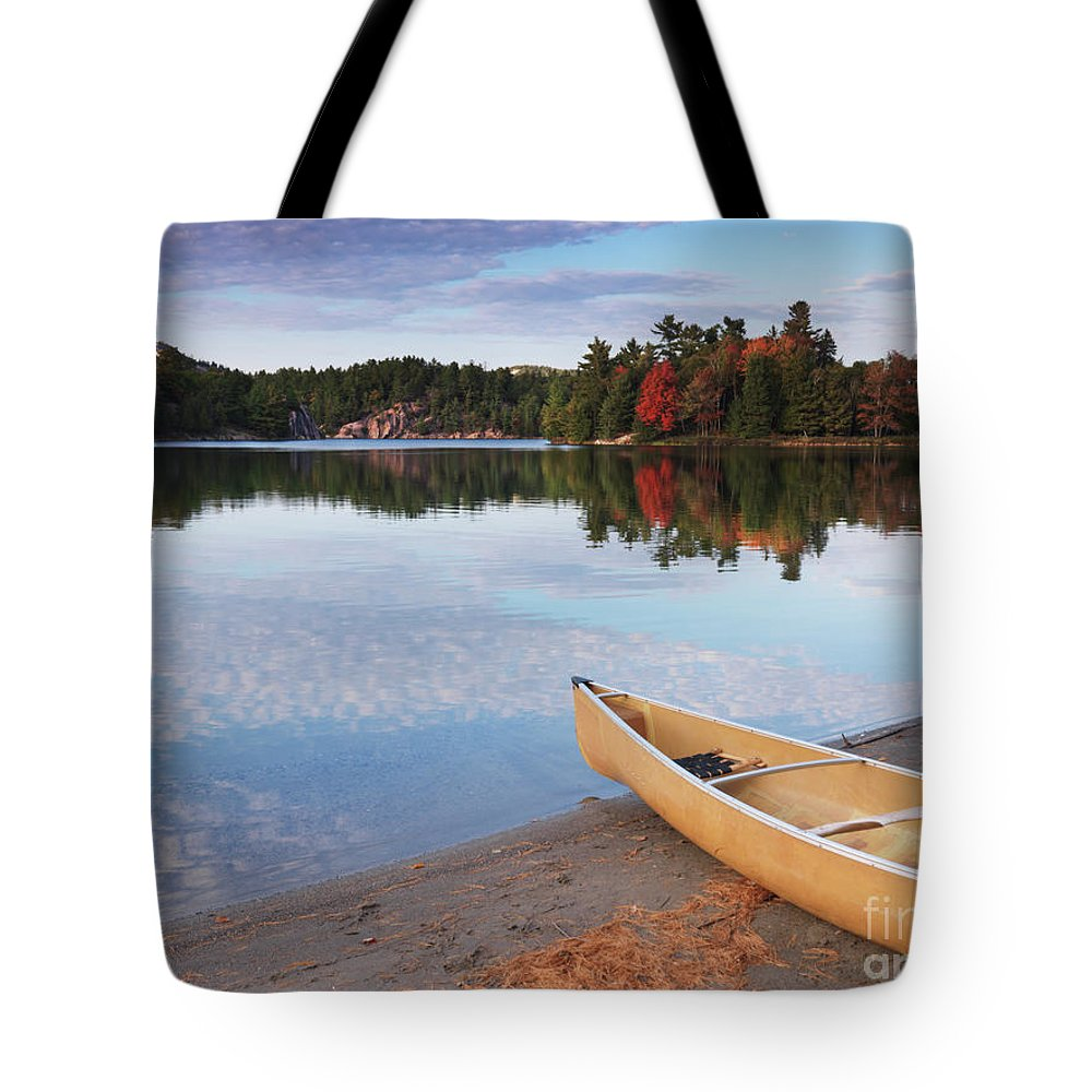 Canoe Tote Bag featuring the photograph Canoe On A Shore Autumn Nature Scenery by Oleksiy Maksymenko