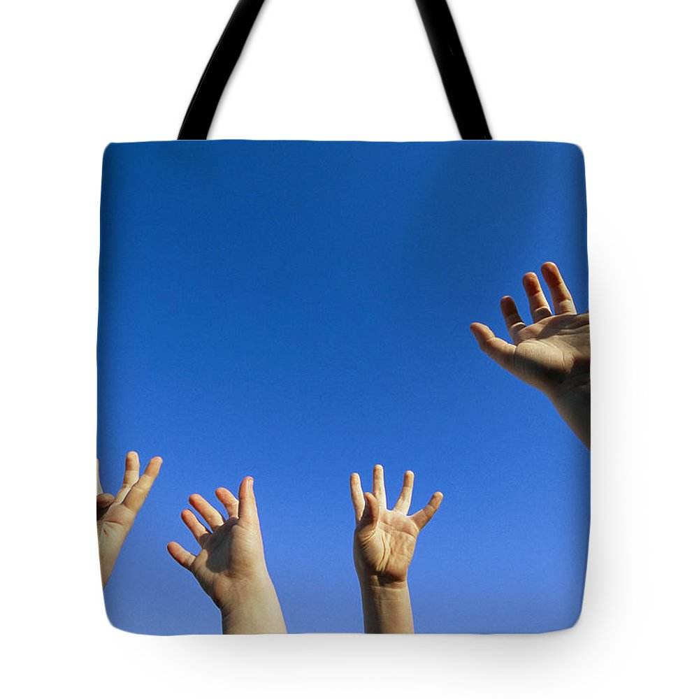 Anatomy Tote Bag featuring the photograph Childrens Hands Reach Toward The Blue by Joel Sartore