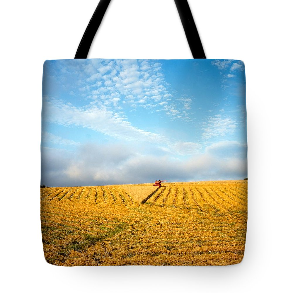Color Image Tote Bag featuring the photograph Combine Harvesting A Wheat Field by The Irish Image Collection