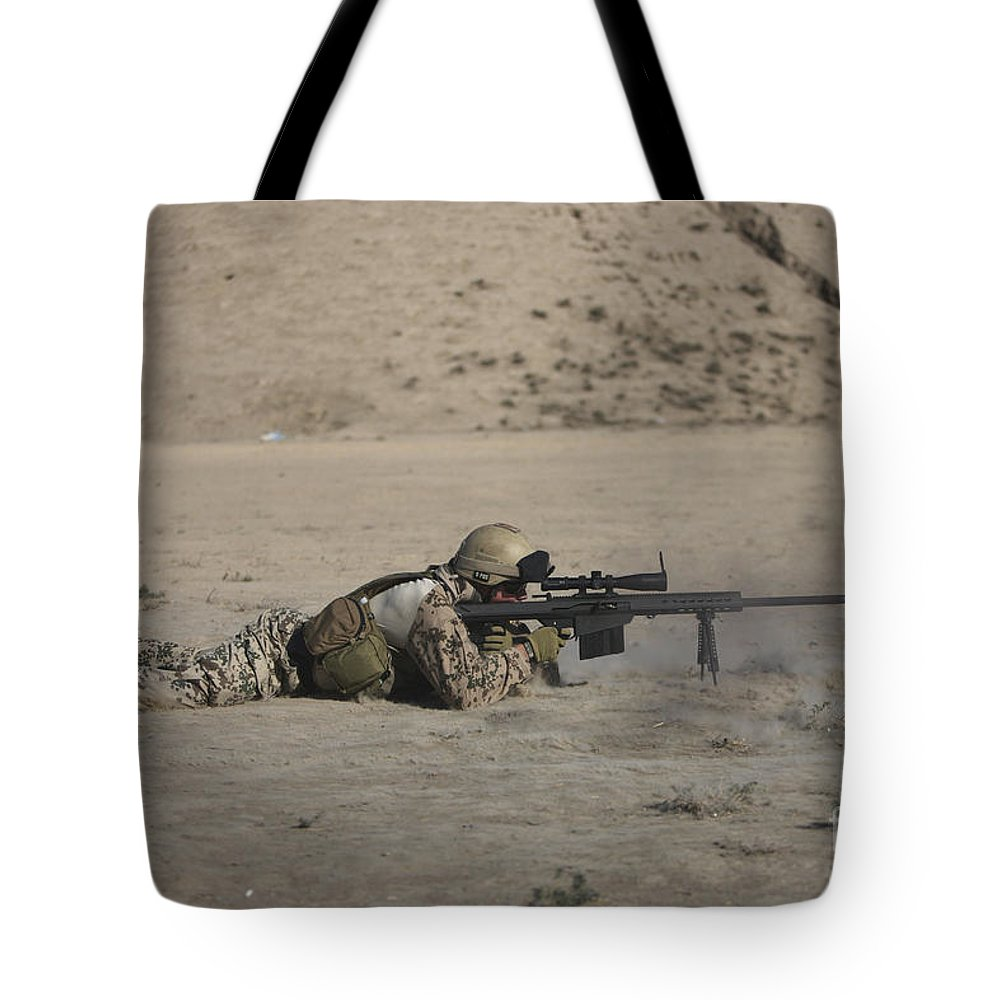 Sniper Tote Bag featuring the photograph German Soldier Firing A Barrett M82a1 by Terry Moore