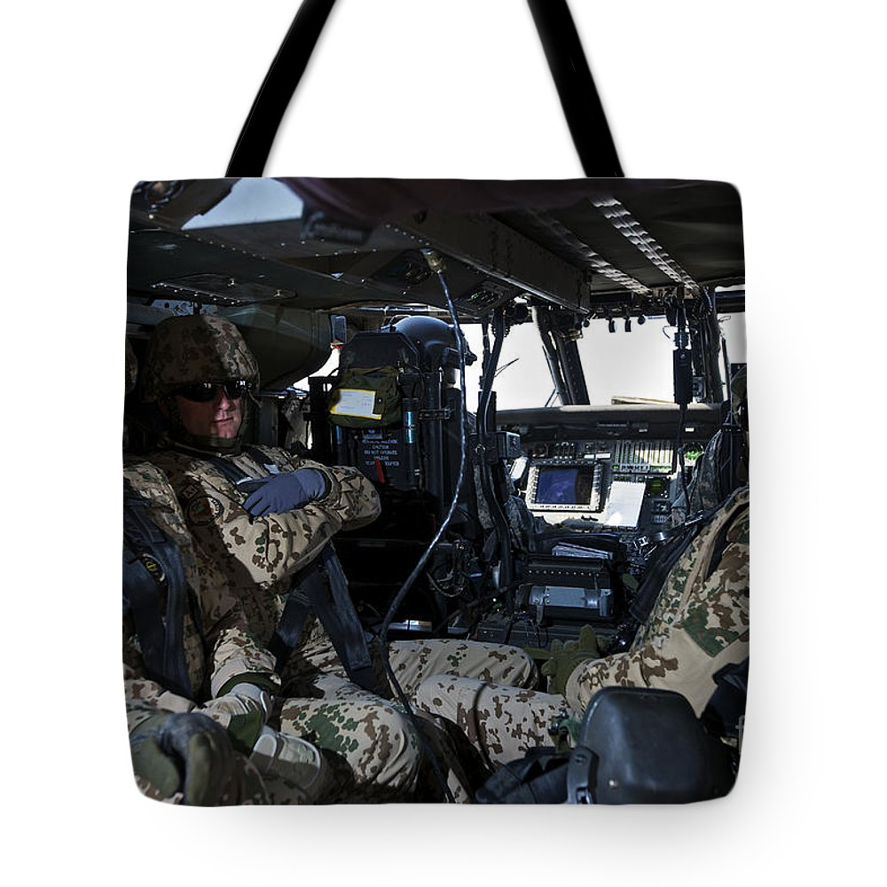 Cockpit Tote Bag featuring the photograph German Soldiers Seated In A Uh-60l by Terry Moore