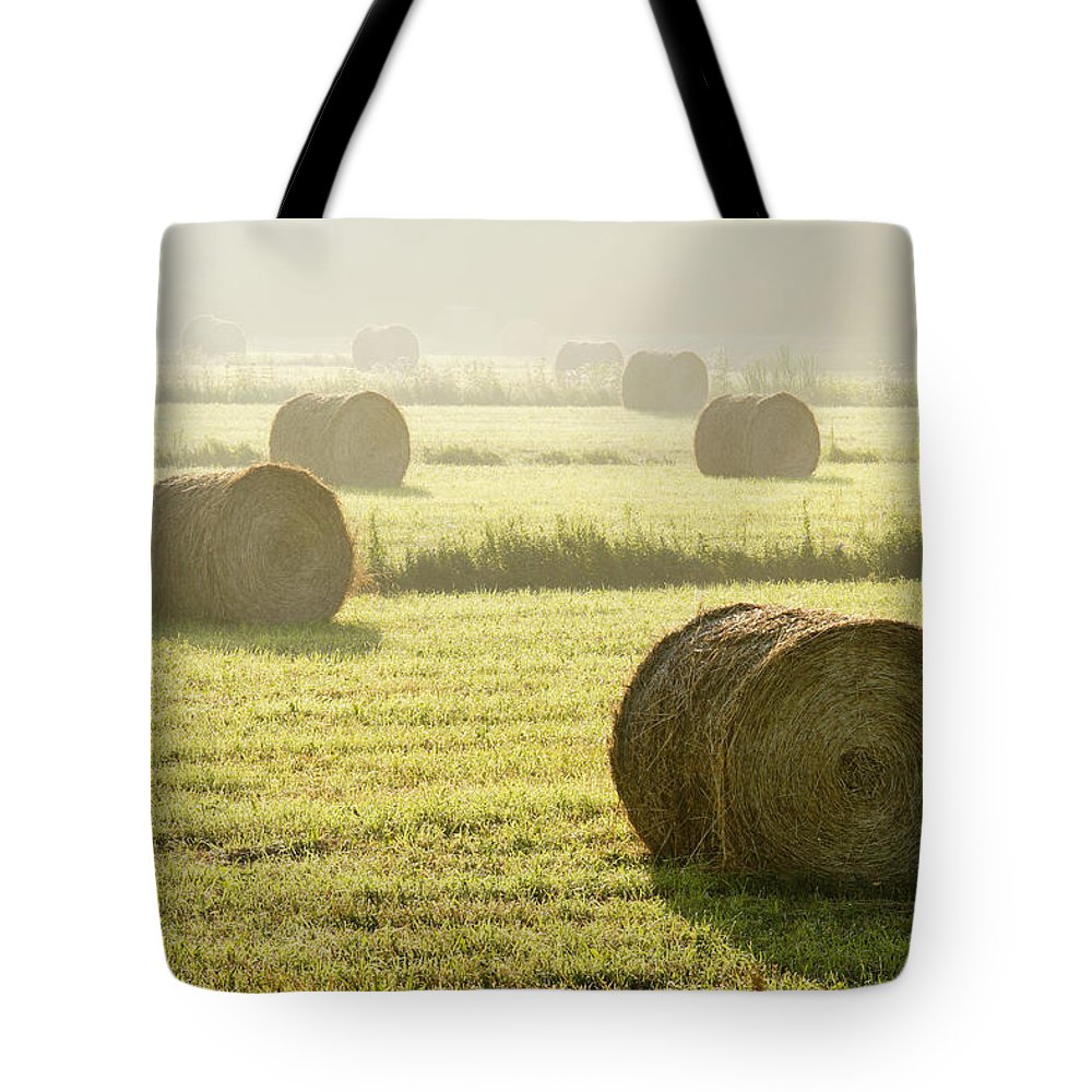 Color Image Tote Bag featuring the photograph Hay Bales In Mist At Sunrise by Yves Marcoux