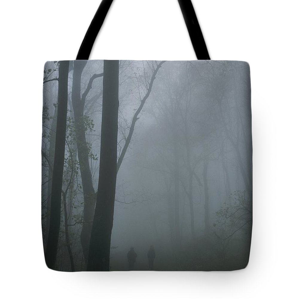 North America Tote Bag featuring the photograph Hikers Enjoy A Foggy Outing On A Trail by George F. Mobley