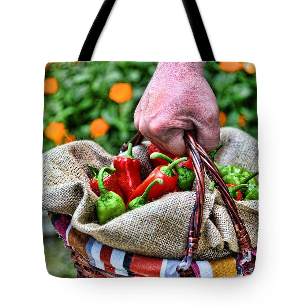 Basket Tote Bag featuring the photograph Man Bringing A Basket Of Red And Green Peperoni by Roberto Giobbi