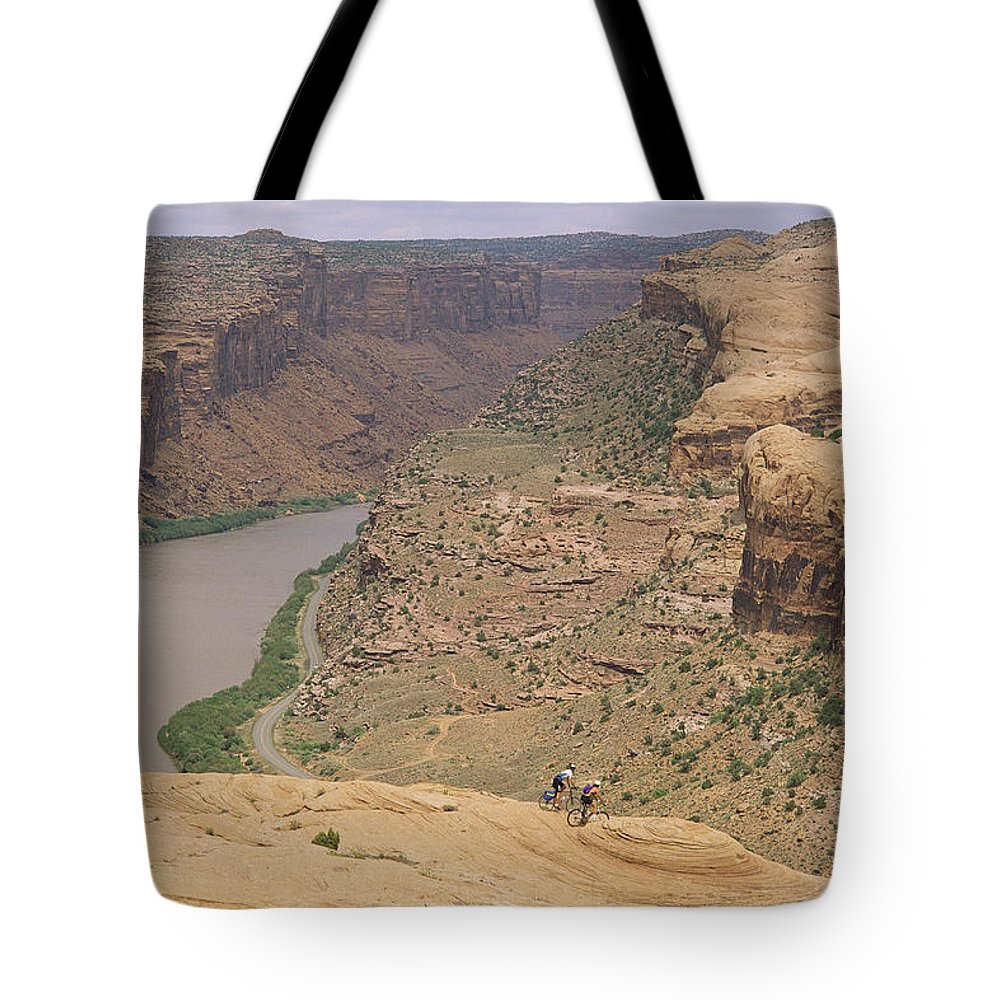 Cycles And Cycling Tote Bag featuring the photograph Mountain Bikers On Slickrock Trail by Rich Reid