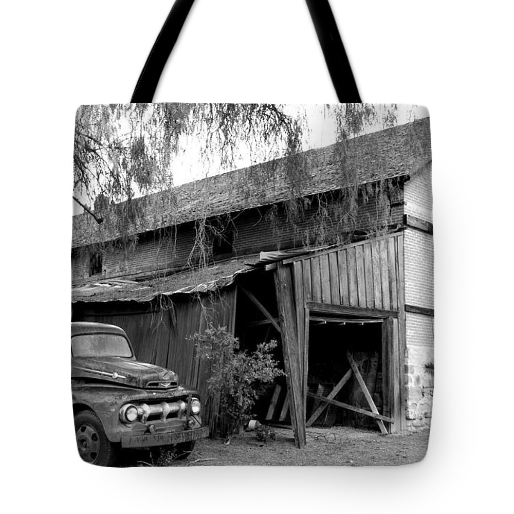 Red barn tote bag featuring the photograph old barn black and white by jeff lowe