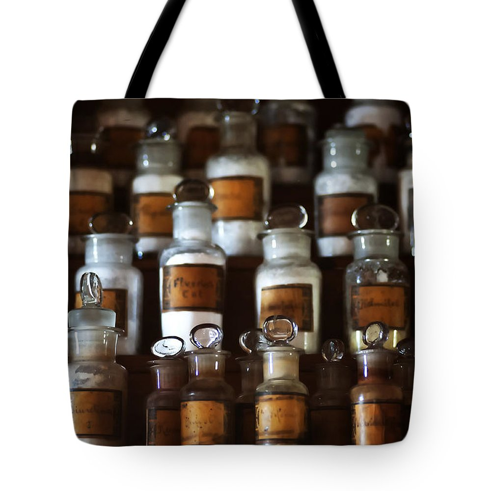 Old Tote Bag featuring the photograph old pharmacy 2 - Old glass bottle with medicine powder of xviii century by Pedro Cardona Llambias