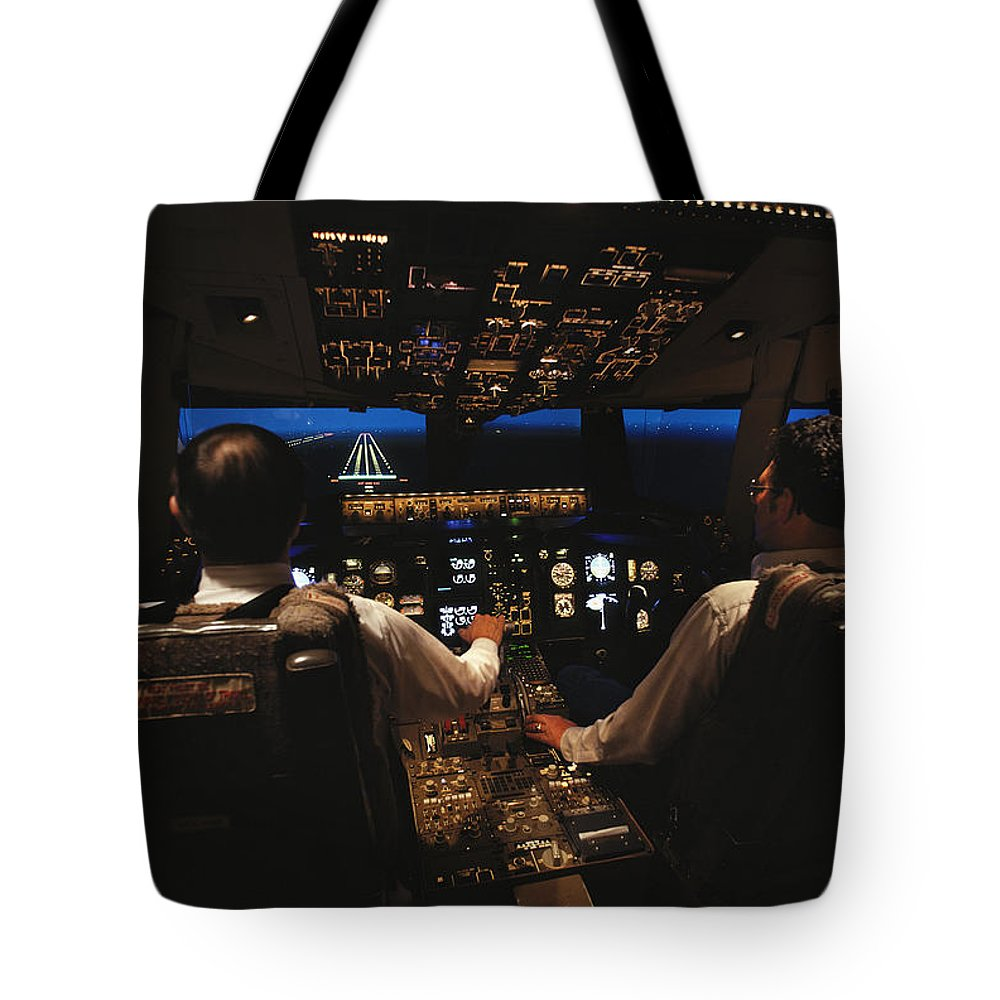 Indoors Tote Bag featuring the photograph Pilots In The Cockpit Of An Aircraft by Paul Chesley