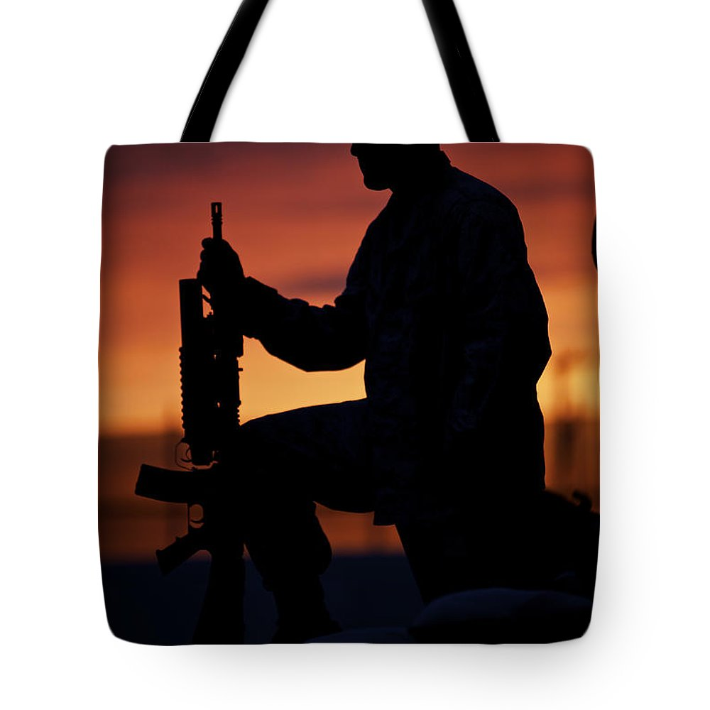 Sandbag Tote Bag featuring the photograph Silhouette Of A U.s Marine On A Bunker by Terry Moore