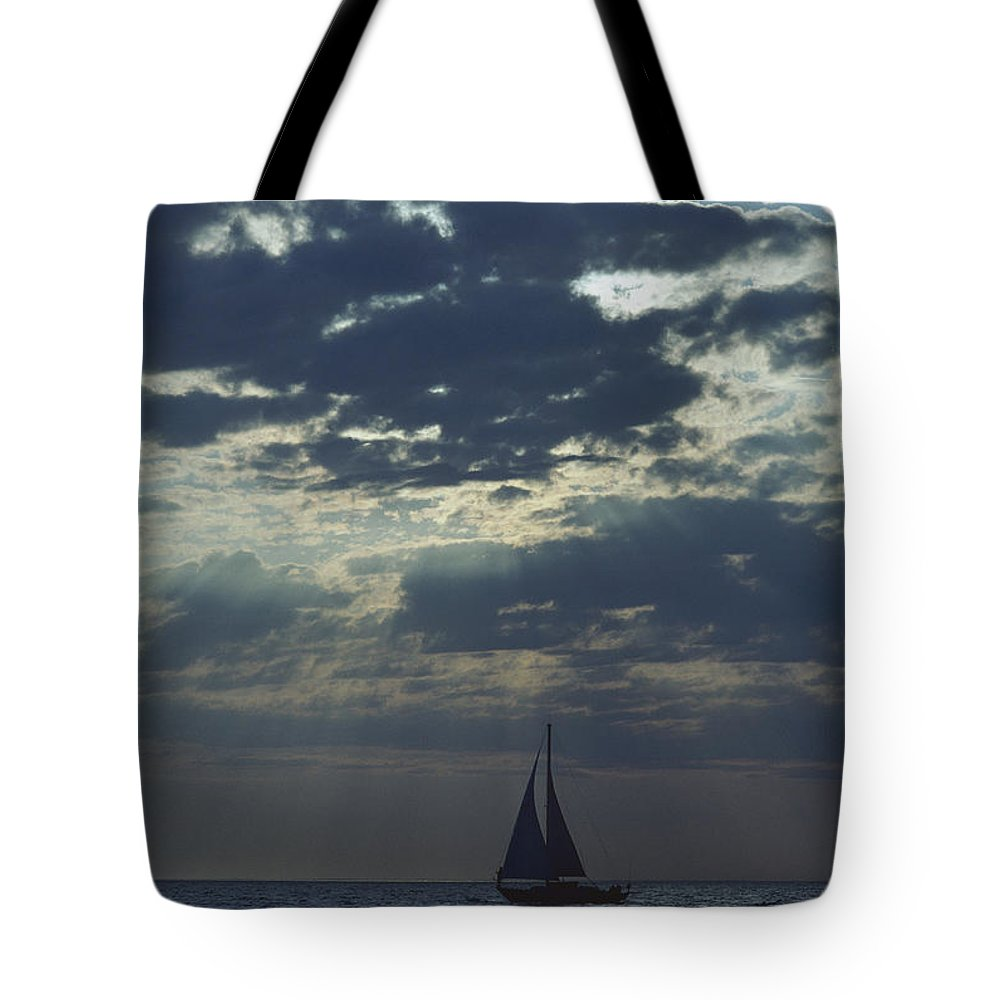 Natural Forces And Phenomena Tote Bag featuring the photograph Sunlight Breaks Through A Cloudy Sky by Todd Gipstein