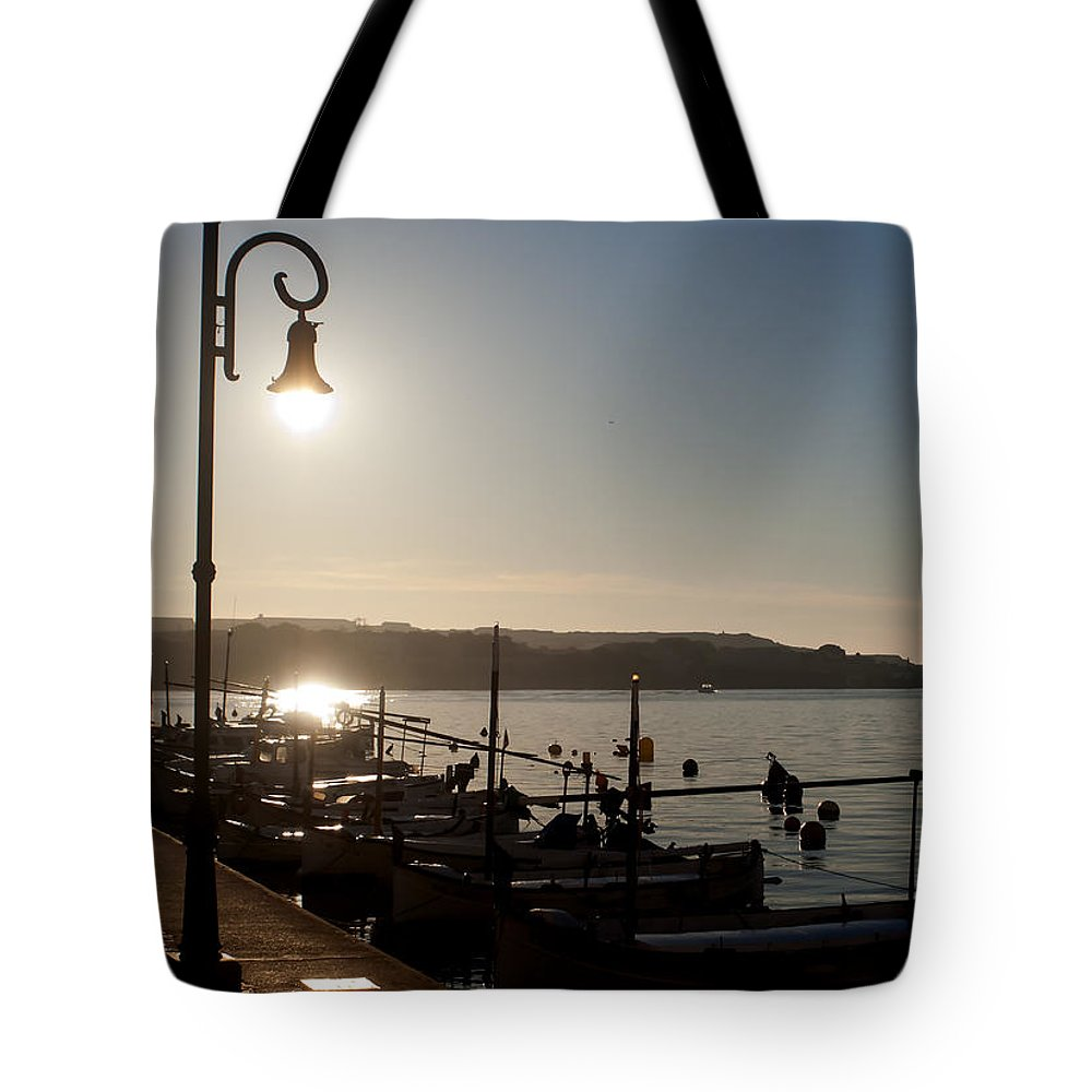 Spain Tote Bag featuring the photograph sunrise - First dawn of a spanish town is Es Castell Menorca sun is a special lamp by Pedro Cardona Llambias