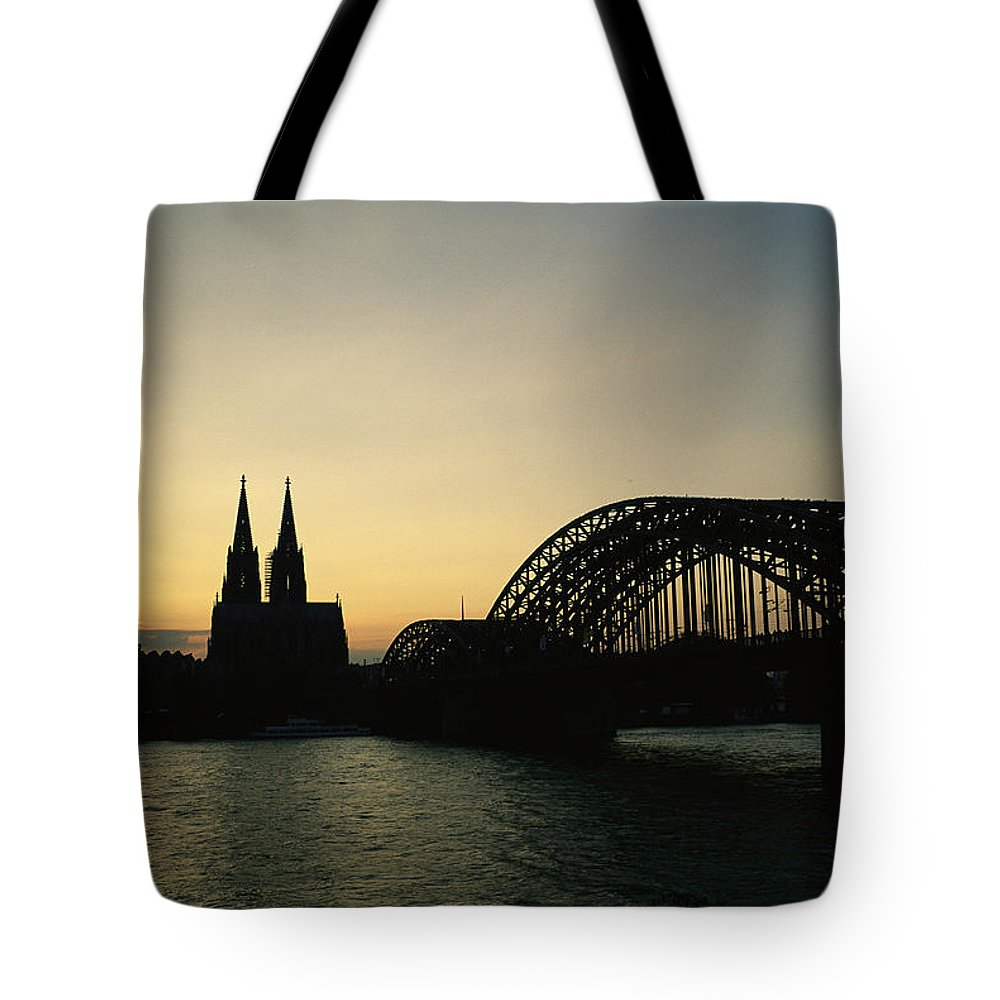 The Cologne Cathedral And Hohenzollern Bridge Silhouetted At Dusk. Tote Bag featuring the photograph The Cologne Cathedral And Hohenzollern by Raul Touzon