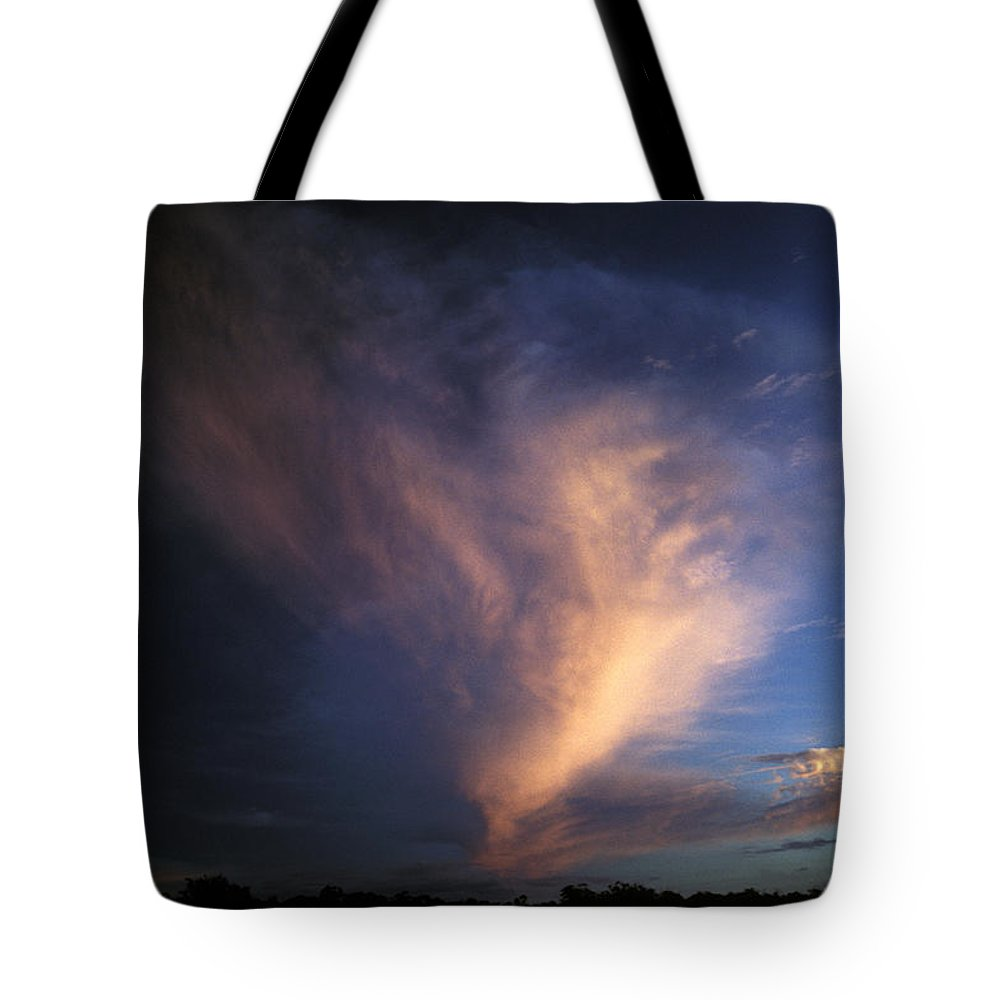Rising Sun Tote Bag featuring the photograph The Rising Sun Reflects Pink Onto An by Jason Edwards