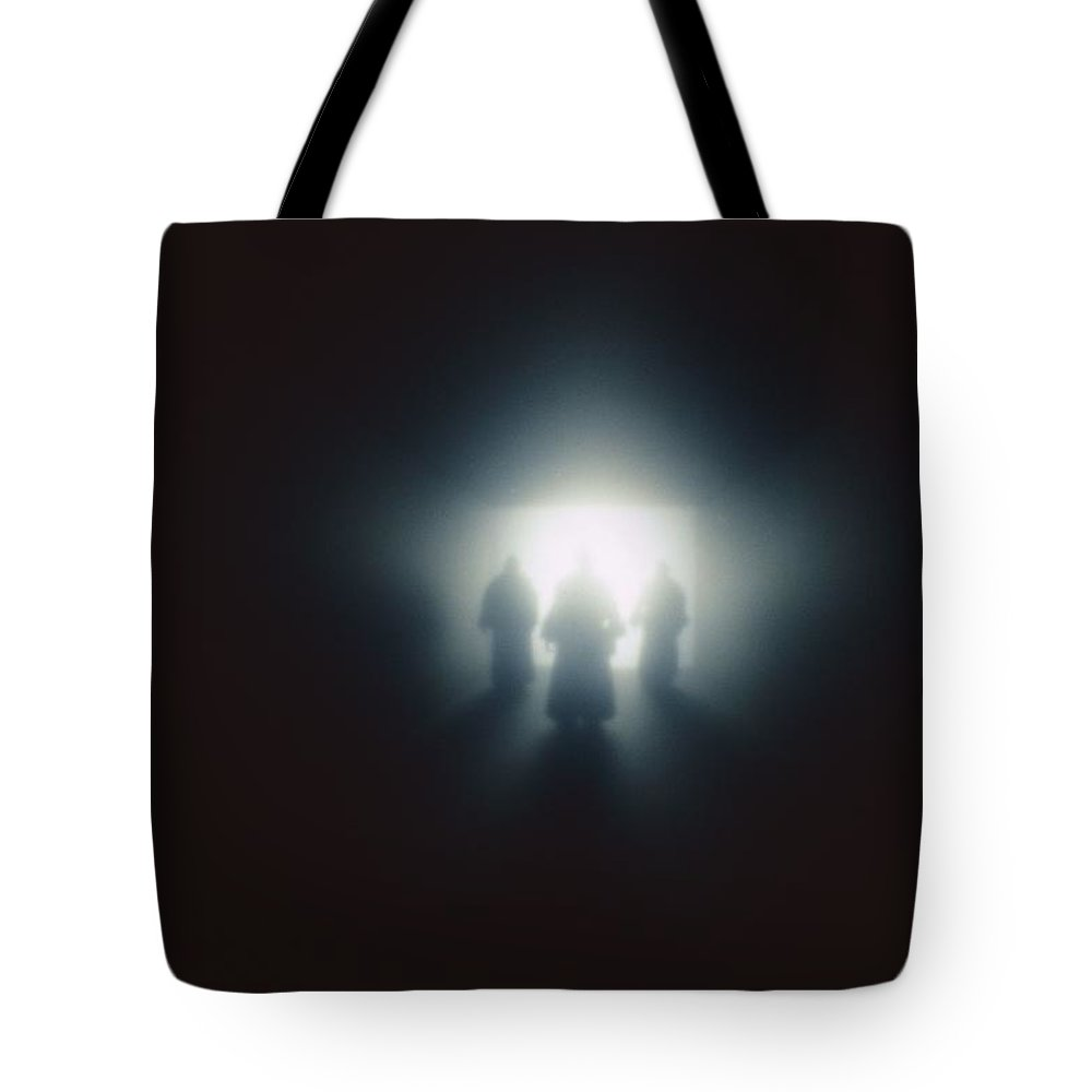 United States Tote Bag featuring the photograph The Silhouette Of Three Figures Dressed by Todd Gipstein