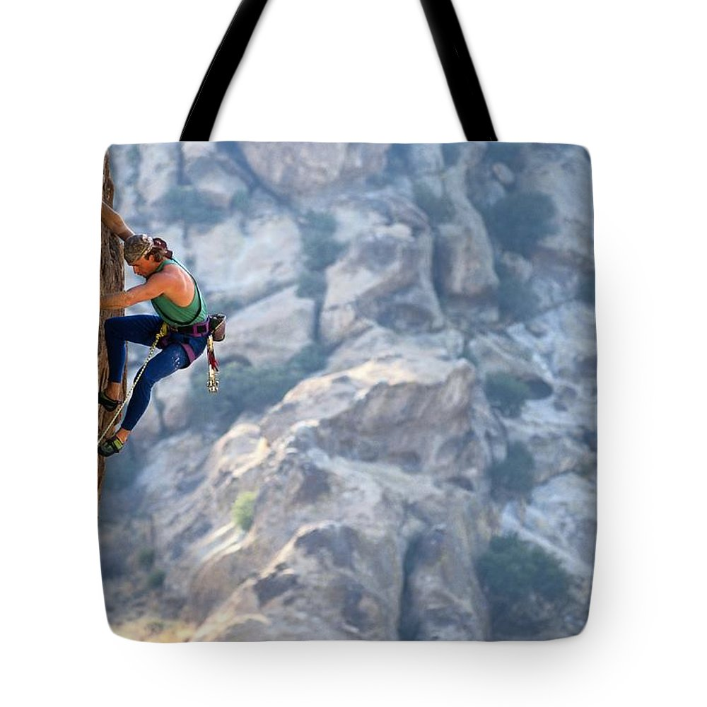 Sports Tote Bag featuring the photograph Todd Skinner Climbing A Rock Face by Bill Hatcher