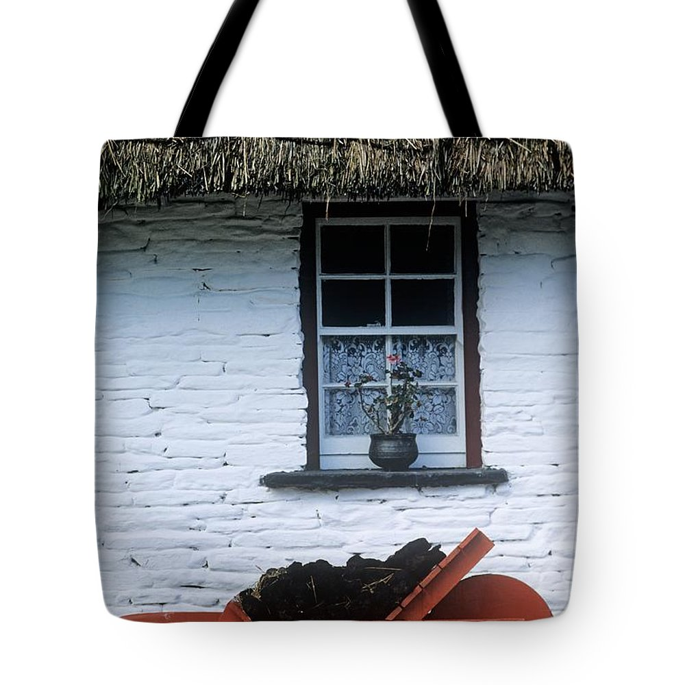 Building Exterior Tote Bag featuring the photograph Wheelbarrow In Front Of A Window Of A by The Irish Image Collection