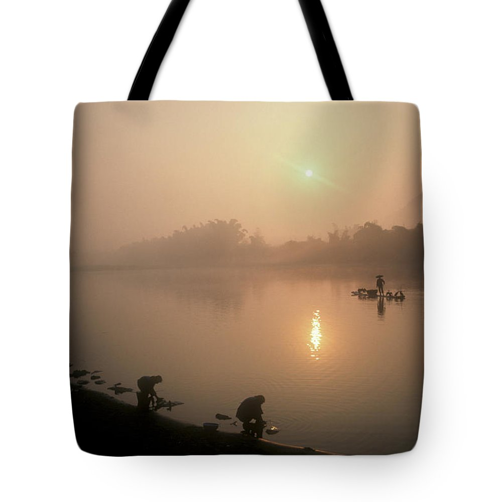 China Tote Bag featuring the photograph Women Wash Clothes At Dawn While by Kenneth Ginn