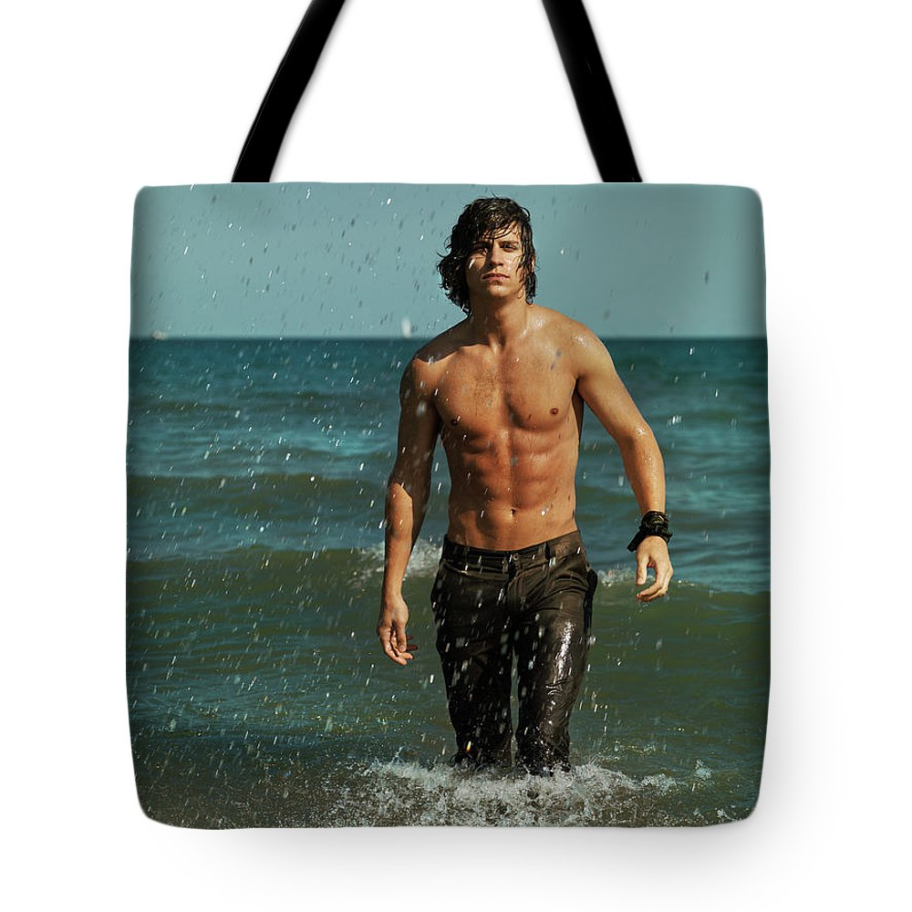 Man Tote Bag featuring the photograph Young Man Walking Out Of The Water by Oleksiy Maksymenko