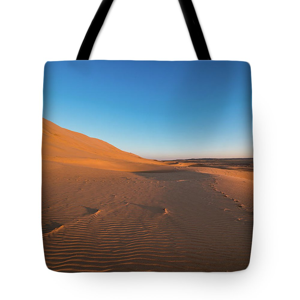 Arid Tote Bag featuring the photograph Dune With Magnificent Sandy Waves At Hot And Windy Morning In Desert by Oleg Yermolov